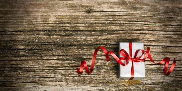 古い木製の背景にクリスマスプレゼント。