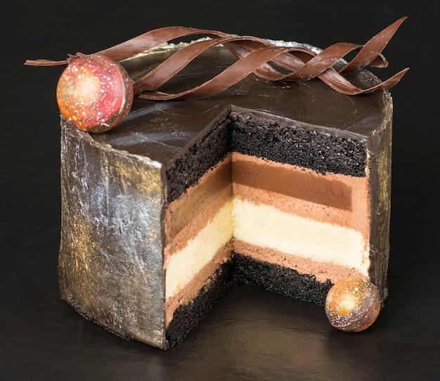 Слои шоколадного торта, украшенные завитками