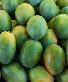 屋外のファーマーズマーケットのクローズアップで展示されている新鮮なカラフルなトロピカルマンゴー。フルーツ。健康的な食事。秋の農業収穫の概念