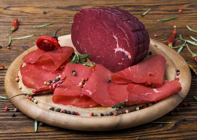木の板にローズマリーと赤唐辛子の小枝でブレサオラをスライス