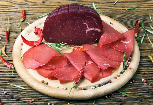 Нарезанная брезаола с веточкой розмарина и красного перца на деревянной доске