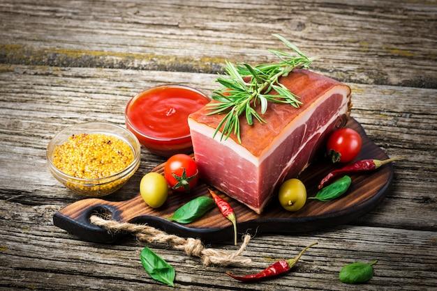 Копченая ветчина на деревянном столе с розмарином, перцем и помидорами черри.