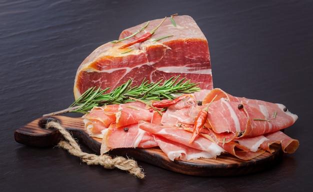 Итальянская прошутто крудо или хамон с розмарином и помидорами. сырая ветчина