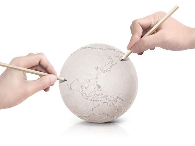 Две руки рисуют карту азии на бумажном шарике на белом фоне