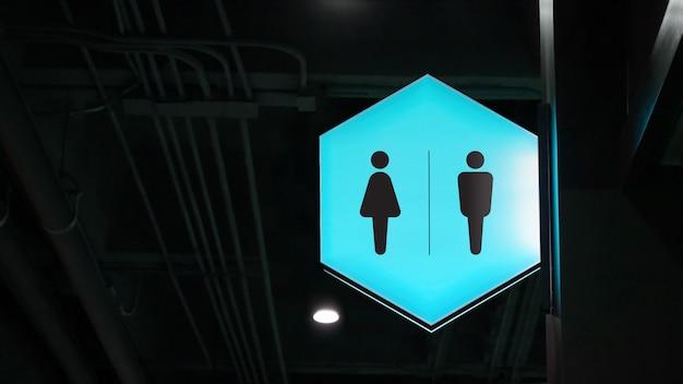 Вывеска для туалета с шестигранной подсветкой висит на стене