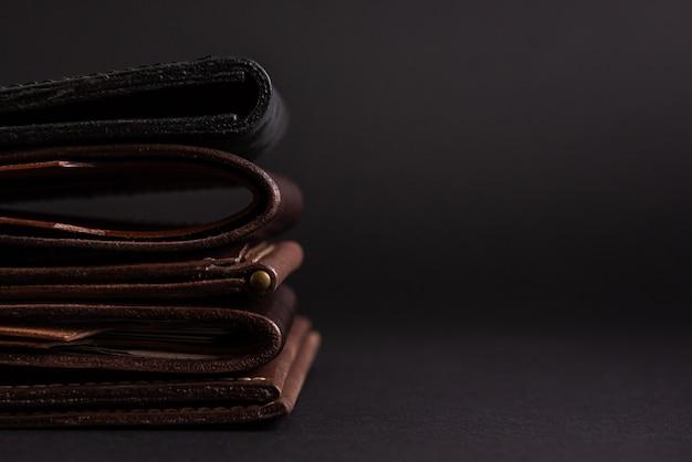 Кожаные кошельки на черном фоне с местом для надписи. кожаная концепция ремесла.