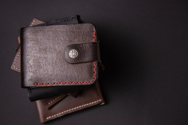碑文のためのスペースと黒の背景に革の財布。レザークラフトのコンセプト。