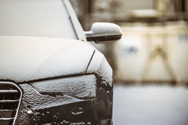 Вид спереди на черный автомобиль, покрытый тонким слоем снега
