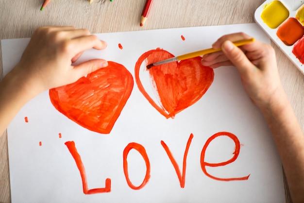 Ребенок рисует акварелью акварелью красное сердце на пейзажном листе на деревянном столе