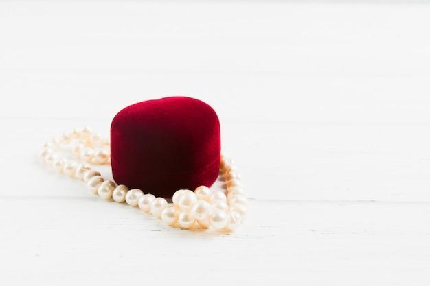 木製の背景に真珠のネックレスと赤い宝石箱