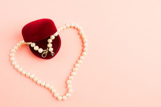 ピンクの背景に開かれたギフトボックスと真珠のネックレス