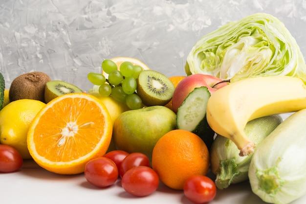 灰色の背景にさまざまな果物や野菜のクローズアップビュー