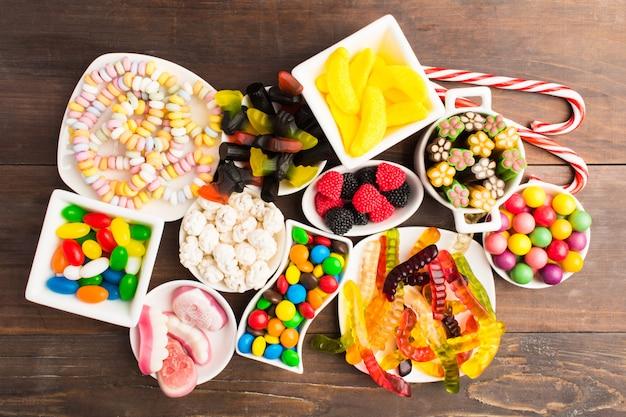 Различные красочные конфеты на белом блюде за деревянным столом