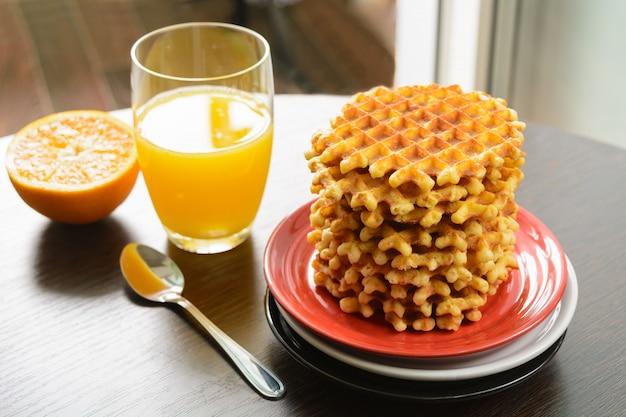 Стопка вафель на тарелках для сервировки и стакан апельсинового сока на завтрак