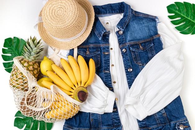 夏の女性のトレンディなファッショナブルな衣装、白い背景の上のトロピカルフルーツを使ったエコバッグ