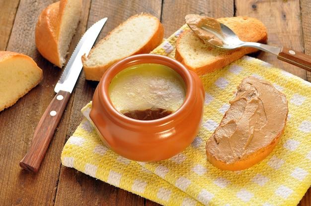 セラミック鍋にパテを入れ、ナプキンにローストします。スプーンと木製の背景上にナイフ