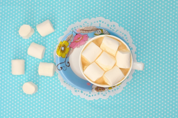 紙ナプキンに青いカップでマシュマロとコーヒー。上面図