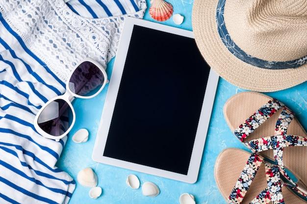 夏の女性のアクセサリー:サングラス、帽子、サンダル、シャツ、青の背景にタブレット