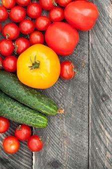 野菜の背景。トマトとキュウリの木製テーブル