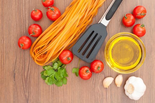 チェリートマト、パスタ、オリーブオイル、ニンニク、ハーブ、パスタトング、古い木製の背景。素朴なスタイル。イタリア料理