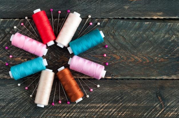 異なる色の糸とピンの古い木製の背景を持つスプール。ミシンアクセサリー