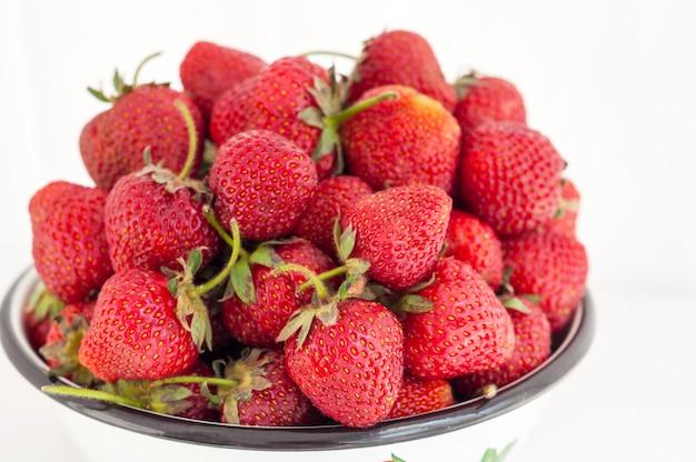 イチゴの果実は、白い背景の上の素朴なボウルでクローズアップ。セレクティブフォーカス