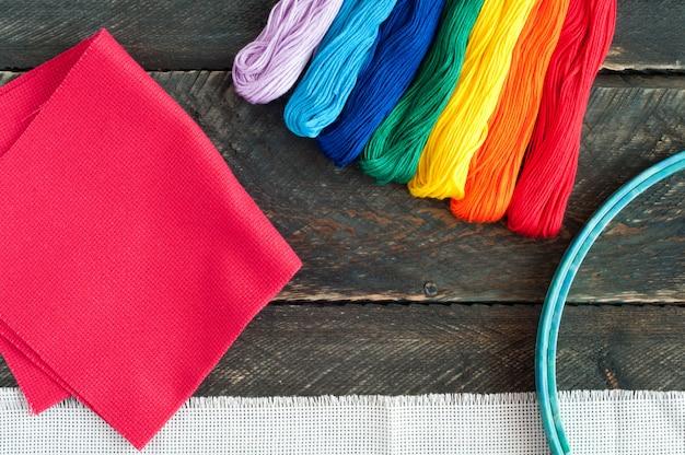 刺繍用アクセサリー。キャンバス、木製の背景に刺繍と糸のフロスのフープ