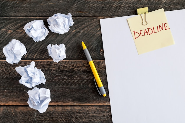 単語の期限付きの付箋。白い空白の紙、しわくちゃの紙、木製の背景のペン