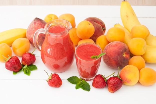 ガラスのミントと白い木製の背景に投手といちごバナナのスムージー。新鮮な果物バナナ、桃、アプリコットの背景