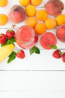 ガラスのミントと白い木製の背景に投手と健康的なイチゴバナナのスムージー。新鮮な果物バナナ、桃、アプリコットの背景