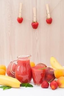ガラスのミントと木製の背景に投手と健康的なイチゴバナナのスムージー。新鮮な果物バナナ、桃、アプリコットの背景