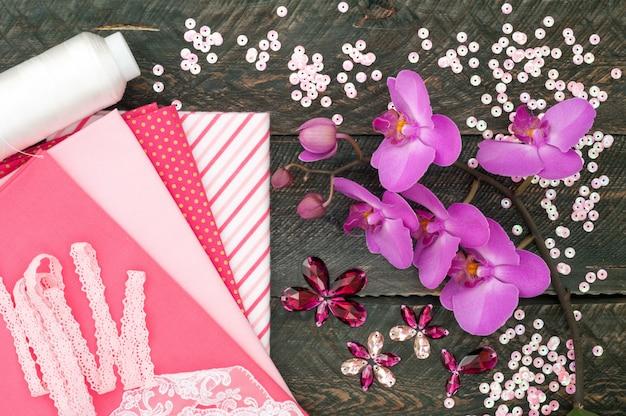 Аксессуары ручной работы. хлопчатобумажная ткань, кружева, катушечная нить, кристаллы и блестки для рукоделия на старых деревянных фоне. цветы орхидеи. вид сверху