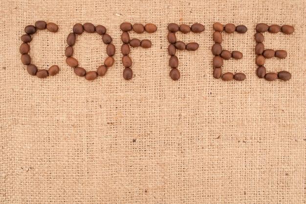 Слово кофе из кофейных зерен на фоне мешковины