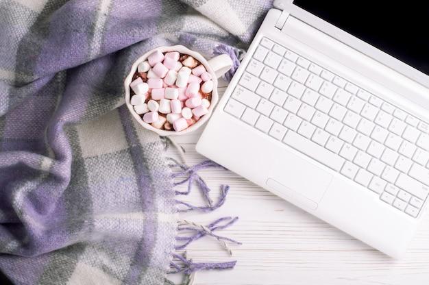 Кофейная чашка, ноутбук и плед. рабочее место в домашнем офисе вид сверху.