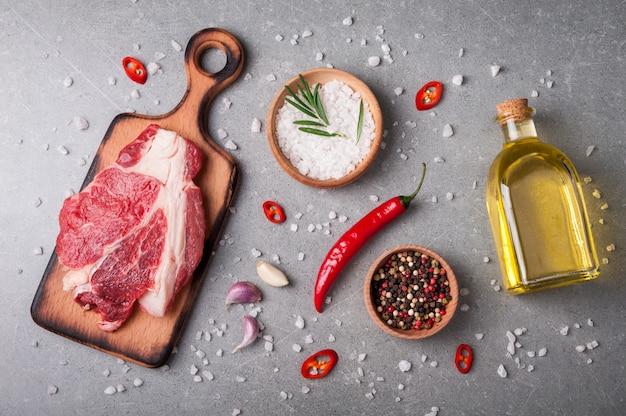 生の肉とスパイスとハーブの灰色の背景