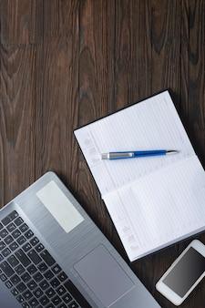 ホームオフィス。検疫所。ノートパソコンとオフィスの机の上のメモ帳。フラット横たわっていた、トップビュー。