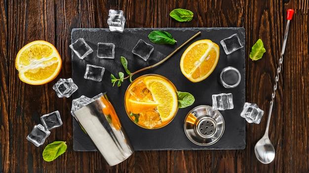 氷を入れたシェーカーで調理したオレンジのデトックスカクテル。リフレッシュメント。グルテンフリードリンク