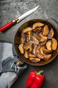 Деревенская еда. жареный картофель на сковороде на темном бетонном столе. деревенский стиль