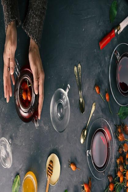 女性の手はローズヒップでお茶を作る。俯瞰図