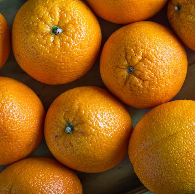 オレンジ色の背景。熟したオレンジのクローズアップ