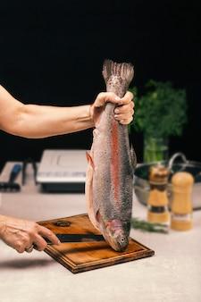 女性は手にサケの魚を握る