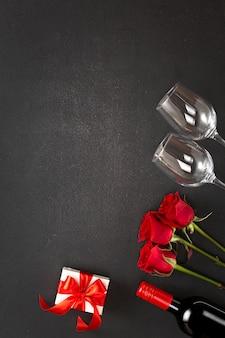 背景女性の日またはバレンタインの日。ワイン、赤いバラ、ギフトボックス。