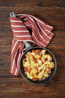 Жареный картофель в сковороде на деревянном столе. вид сверху.