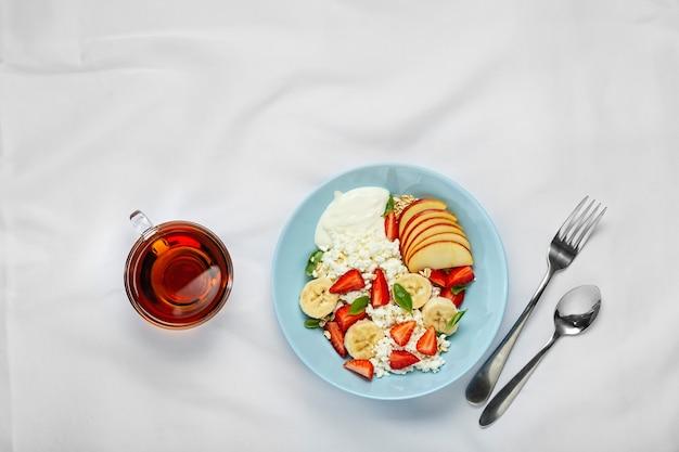 Фруктовый салат. фруктовый десерт со взбитыми сливками, клубникой, творогом, мятой и мюсли