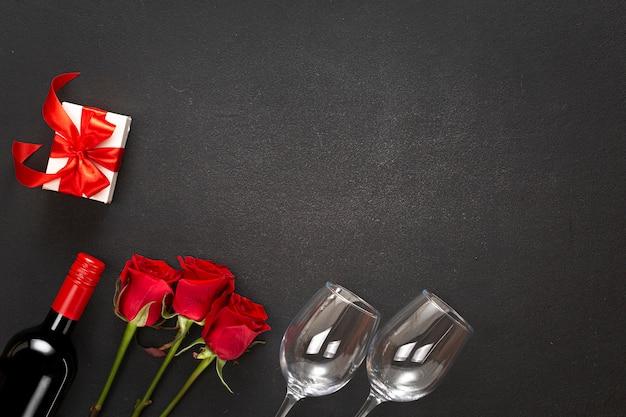 ワイン、バラ、赤いリボン付きギフトボックス。愛の概念
