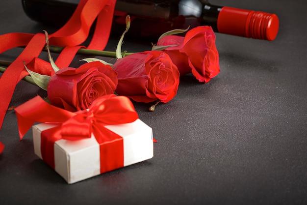 バレンタインデーの組成物。赤いバラの花、ワイン、ギフトボックス。上面図