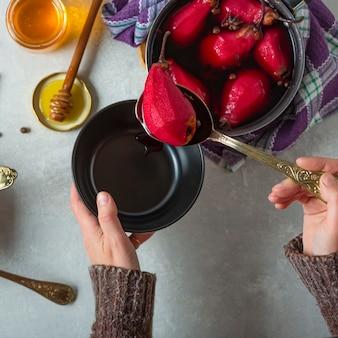 グリューワインで煮た梨。女性は梨をボウルに入れます。