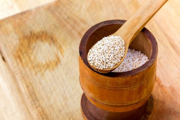 Семена амаранта на деревянной банке и ложке, деревенский деревянный столик