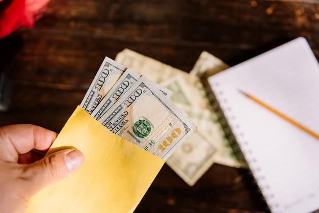 Деньги - рука, держащая конверт с долларовыми купюрами