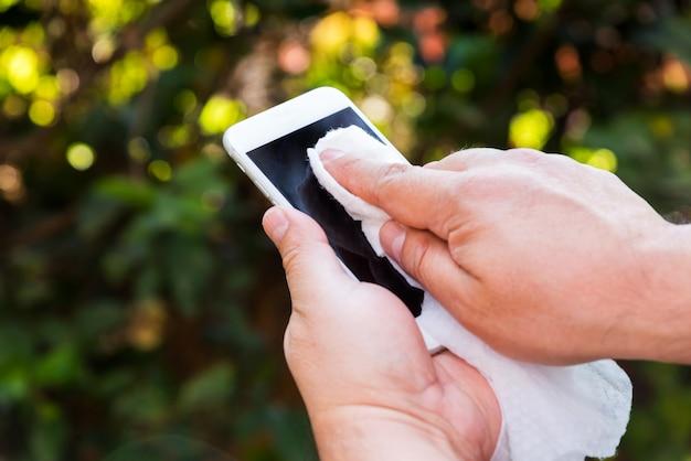 携帯電話を保持して掃除する手